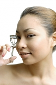 Young woman using eyelash curler, looking at camera - Asia Images Group