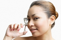 Young woman holding eyelash curler, looking at camera - Asia Images Group