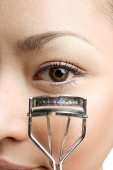 Young woman holding eyelash curler near eye, close up - Asia Images Group