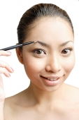 Young woman using eyebrow pencil - Asia Images Group