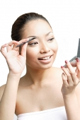 Young woman using eyebrow brush, looking away - Asia Images Group