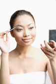 Young woman using eyebrow brush, looking at compact - Asia Images Group