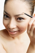 Young woman using eyebrow brush, looking at camera - Asia Images Group
