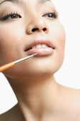 Woman using lipstick brush, portrait - Asia Images Group