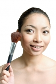 Woman holding make-up brush - Asia Images Group