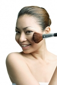 Woman applying blusher with make-up brush, smiling at camera - Asia Images Group