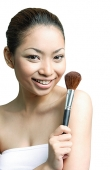 Woman holding make-up brush, smiling at camera - Asia Images Group