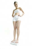 Young woman standing on weighing scale, hands on hips - Asia Images Group