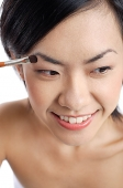 Woman applying eyeshadow - Asia Images Group