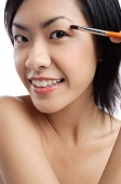 Woman holding brush, applying eyeshadow - Asia Images Group