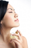 Woman applying perfume, sideview - Asia Images Group