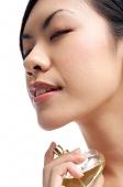 Woman holding perfume bottle, spraying on neck, eyes closed - Asia Images Group