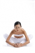 Woman sitting on floor, stretching - Asia Images Group