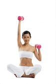 Woman sitting crossed legged on floor, lifting dumbbells, looking at camera - Asia Images Group