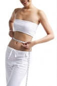 Woman standing, holding tape measure around waist - Asia Images Group