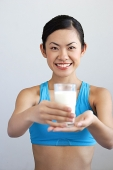 Woman holding glass of milk - Asia Images Group