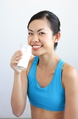 Woman drinking glass of milk, smiling at camera - Asia Images Group