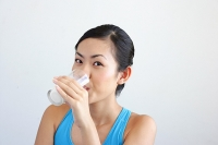 Woman drinking glass of milk, looking at camera - Asia Images Group