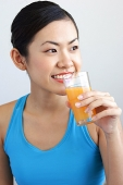 Woman holding glass orange juice to mouth, looking away - Asia Images Group