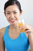 Woman holding glass orange juice looking at camera - Asia Images Group