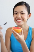 Woman holding grapefruit and spoon, looking at camera - Asia Images Group
