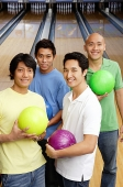 Men in bowling alley, holding bowling balls, looking at camera - Asia Images Group