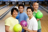 Four men in bowling alley, holding bowling balls - Asia Images Group