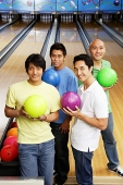 Four men standing in bowling alley, holding bowling balls - Asia Images Group