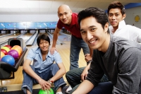 Four men in bowling alley, looking at camera - Asia Images Group
