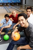 Four men in bowling alley, smiling at camera - Asia Images Group