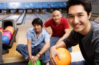 Three men in bowling alley, smiling at camera - Asia Images Group