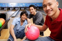 Three men in bowling alley, looking at camera - Asia Images Group