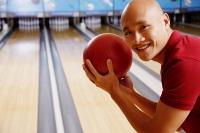 Man holding bowling ball, smiling at camera - Asia Images Group