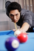 Man holding pool cue, aiming at ball - Asia Images Group