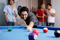Man aiming pool cue at ball, other men watching in the background - Asia Images Group