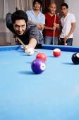 Man playing pool, other men watching in the background - Asia Images Group