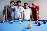 Men standing around pool table, looking at camera - Asia Images Group