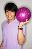 Man carrying bowling ball, smiling at camera - Asia Images Group