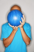Man holding bowling ball in front of face - Asia Images Group