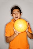 Man holding bowling ball, smiling at camera - Asia Images Group