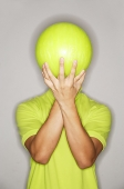 Man holding bowling ball in front of his face - Asia Images Group