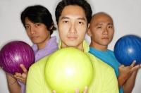 Three men holding bowling balls, looking at camera - Asia Images Group