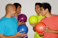 Four men holding bowling balls, smiling - Asia Images Group