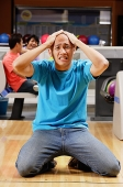 Man kneeling in bowling alley, hands on head, grimacing - Asia Images Group