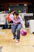 Man bowling, people watching in the background - Asia Images Group