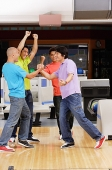 Four guys at a bowling alley, arms raised in victory - Asia Images Group