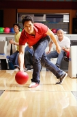 Man bowling, friends watching in the background - Asia Images Group