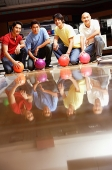 Four men in bowling alley, crouching, holding bowling balls - Asia Images Group