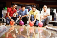 Four men crouching in bowling alley, holding bowling balls - Asia Images Group