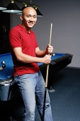 Man leaning against pool table, looking at camera - Asia Images Group